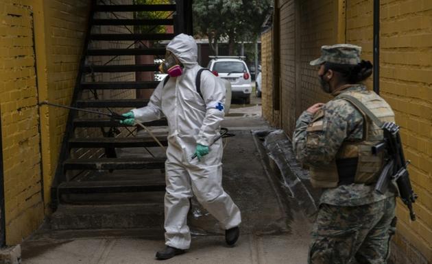Un employé municipal désinfecte un immeube à Santiago le 16 juin 2020 [Martin BERNETTI / AFP]