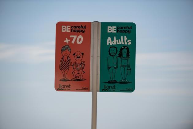 Un panneau indique les espaces réservés aux diffférents âges sur la plage de Lloret de Mar, le 22 juin 2020 en Espagne [Josep LAGO / AFP]