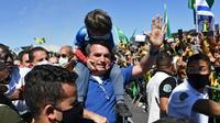 Le président brésilien Jair Bolsonaro porte le fils d'un de ses partisans lors d'un rassemblement à Brasilia le 31 mai 2020 [EVARISTO SA / AFP]