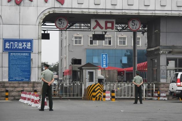 Des policiers chinois devant l'entrée du marché Xinfadi fermé, le 13 juin 2020 à Pékin, après l'apparition d'un nouveau foyer de coronavirus [GREG BAKER / AFP]