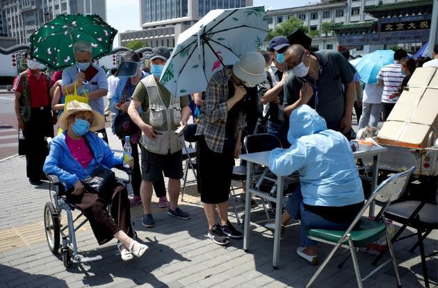 Des Chinois attendent pour se faire tester au coronavirus, le 17 juin 2020 à Pékin, après l'apparition de nouveaux cas [Noel Celis / AFP]