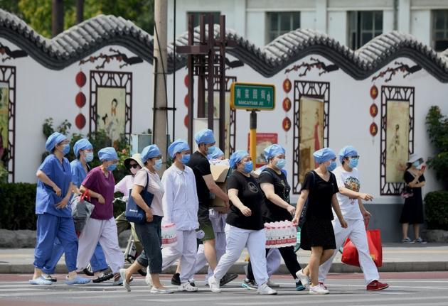 Des membres du personnel médical se préparent à tester les habitants vivant près du marché Xinfadi, nouveau foyer de coronavirus à Pékin, le 16 juin 2020 [Noel Celis / AFP]
