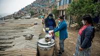 Une religieuse sert de la nourriture dans une soupe populaire d'un quartier pauvre de Lima (Pérou) le 28 mai 2020, où les habitants souffrent de la crise économique entraînée par la pandémie de nouveau coronavirus  [Ernesto BENAVIDES / AFP]