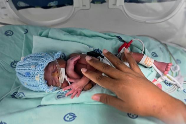 Diana Angola, atteinte par le coronavirus, caresse son fils Jefferson placé en couveuse à la clinique de Versalles, le 23 juin 2020 à Cali, en Colombie [Luis ROBAYO / AFP]