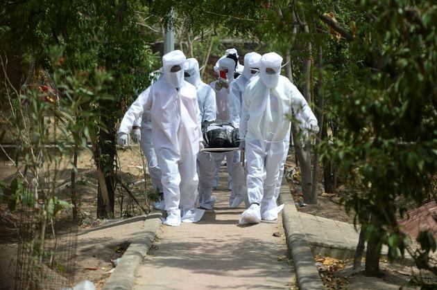 Des volontaires portent le cercueil d'un mort du Covid-19 dont le corps n'a pas été réclamé, à Chennai le 16 juin 2020 [Arun SANKAR / AFP]