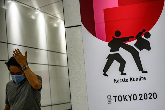 Un passant, portant un masque chirurgical, près d'une affiche liée à l'épreuve de karaté des Jeux de Tokyo, le 12 juin 2020 dans l'arrondissement de Shinjuku. [Philip FONG / AFP]