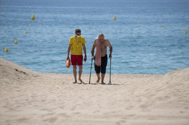 Un secouriste, portant un masque de protection, accompagne un homme âgé sur la plage de Lloret de Mar, le 22 juin 2020 en Espagne [Josep LAGO / AFP]