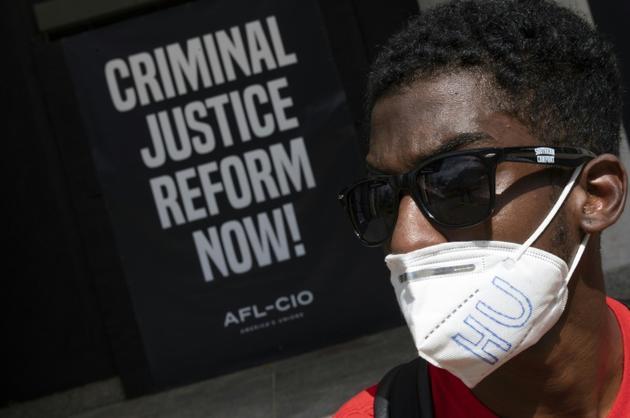 Moah Pollas, pose devant une pancarte peinte près du parc Lafayette, à proximité de la Maison Blanche, à Washington, le 5 juin 2020 [Roberto SCHMIDT / AFP]