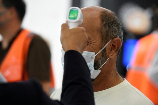 Contrôle de la température d'un passager à l'aéroport d'Orly le 26 juin 2020 [ERIC PIERMONT / AFP]