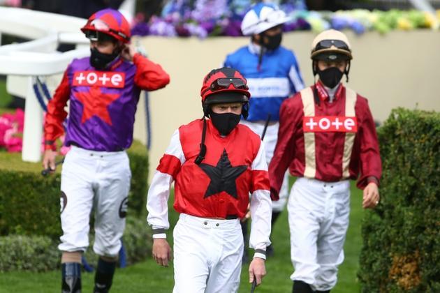 Des jockeys portent des masques pour la course de Kings Stand Stakes, qui s'est déroulée à huis-clos à Ascot, dans l'ouest de Londres, le 16 juin 2020 [Julian Finney / POOL/AFP]