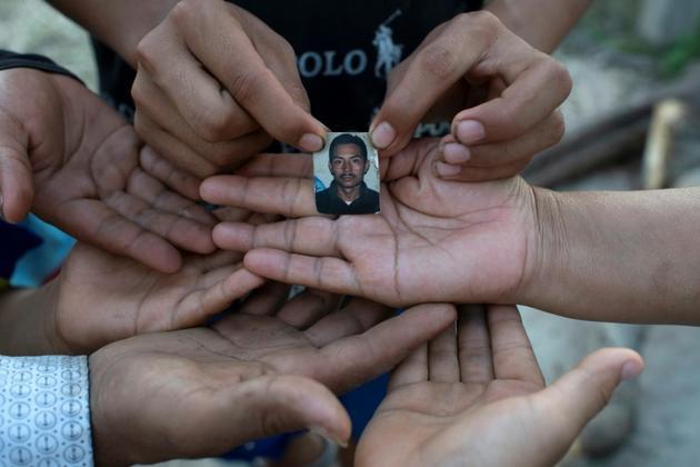 Une veuve et ses cinq enfants montrent le 23 juillet 2020 une photo de leur époux et père, Joaquin Barrera, mort du Covid-19 comme ses parents et deux de ses frères à Santiago Nonualco, au Salvador</p> <p> [Yuri CORTEZ / AFP]