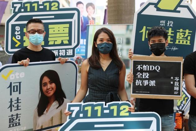 Gwyneth Ho (C), candidate aux primaires du camp pro-démocratie à Hong Kong, aux côtés d'Anthony Wong (G) et Lester Shum (D), le 11 juillet 2020 [May JAMES / May James/AFP]