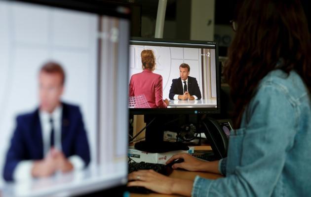 Retransmission de l'entretien télévisé d'Emmanuel Macron avec deux journalistes, le 14 juillet 2020 [Stefano RELLANDINI / AFP]