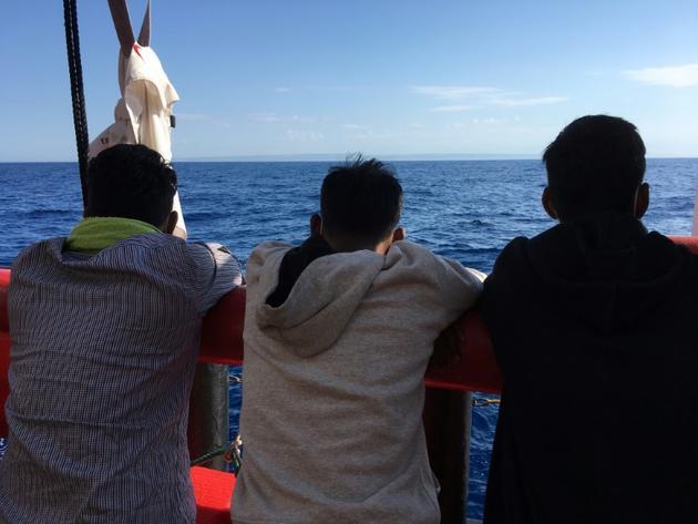 Des migrants secourus en mer regardent les côtes siciliennes depuis le navire humanitaire Ocean Viking, le 5 juillet 2020 en Méditerranée   [Shahzad ABDUL / AFP]