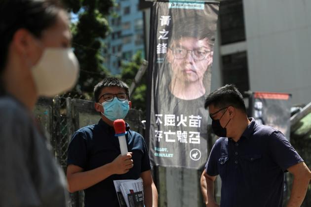 Le militant pro-démocratie Joshua Wong (C), candidat pour les primaires organisées par son camp, durant le scrutin à Hong Kong le 11 juillet 2020 [May JAMES / May James/AFP]