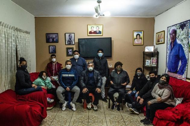 Les membres de la famille Diaz à l'issue d'une messe en ligne à la mémoire de Cecilio Diaz, 81 ans, mort du coronavirus il y a un mois, le 11 août 2020 à Chorrillos, au sud de Lima, au Pérou [Ernesto BENAVIDES / AFP]