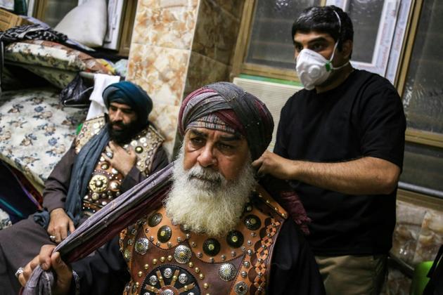 Un homme masqué aide un vieille homme à mettre son costume avant une célébration chiite à Karbala, en Irak, le 22 août 2020 [Mohammed SAWAF / AFP]
