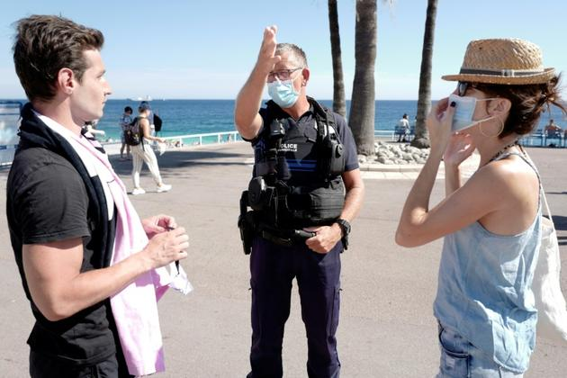 Des policiers informent les passants sur la promenade des Anglais à Nice de l'obligation de porter le masque, le 3 août 2020<br />  [VALERY HACHE / AFP]