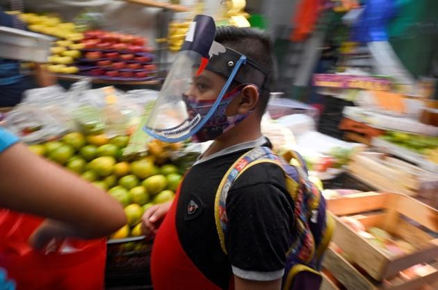 Un jeune garçon porte un masque en plexiglas au marché de San Cosme à Mexico le 10 août 2020<br />  [Alfredo ESTRELLA / AFP]