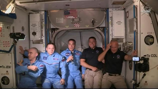 Image transmise par la Nasa de Robert Behnken (2e d) et Doug Hurley (d), à leur arrivée dans l'ISS, avec les autres astronautes de la station spatiale, le 31 mai 2020 [Handout / NASA TV/AFP/Archives]