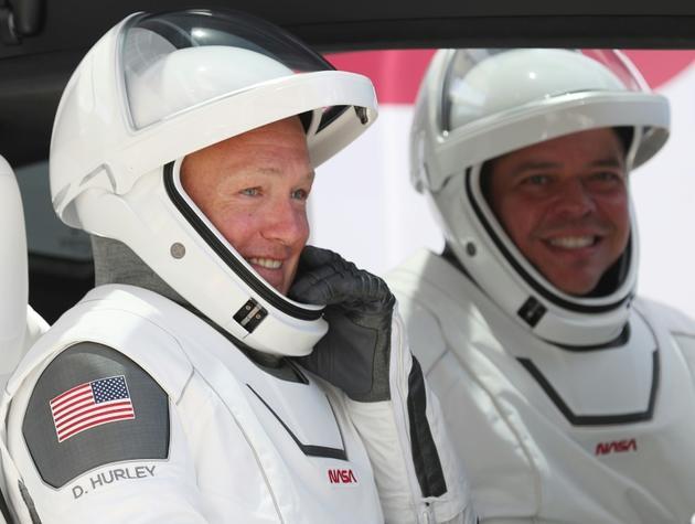 Les astronautes américains Bob Behnken (d) et Doug Hurley avant leur décollage à bord de la capsule Crew Dragon de SpaceX, le 30 mai 2020 à Cap Canaveral, en Floride [JOE RAEDLE / GETTY IMAGES NORTH AMERICA/AFP/Archives]