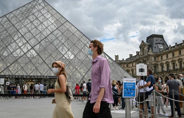 Des touristes passent devant la Pyramide du Louvre conçue par l'architecte Ieoh Ming Pei, le 15 août 2020 à Paris [BERTRAND GUAY / AFP]