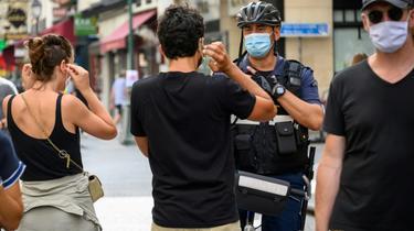Un policier municipal demande à des passants de porter un masque de protection, le 15 août 2020 à Paris [BERTRAND GUAY / AFP]
