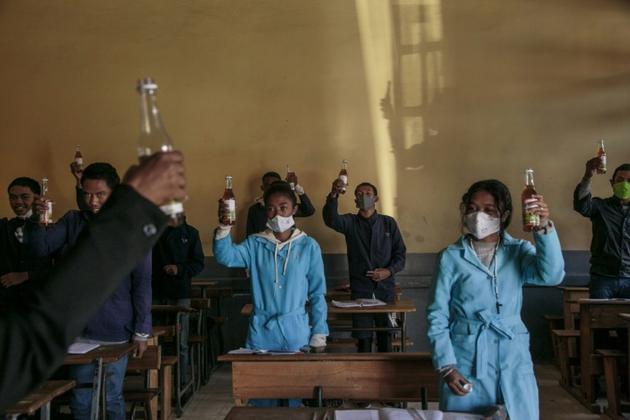 Des étudiants brandissent des bouteilles de Covid Organics, une tisane à base de plantes présentée comme un remède au coronavirus par le président malgache Andry Rajoelina, à Antananarivo loe 23 avril 2020 [RIJASOLO / AFP]