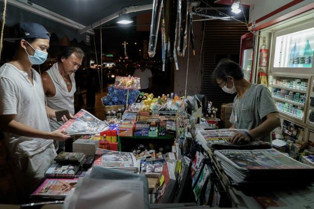 Des clients achètent le tabloïd Apple Daily du 11 août 2020 au lendemain de l'arrestation de son patron prodémocratie, Jimmy Lai, à Hong Kong [Yan ZHAO / AFP]