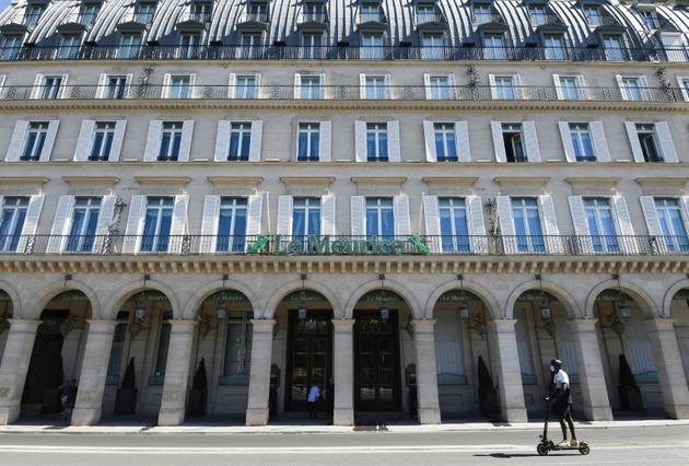 Un homme en trottinette passe devant le grand hôtel Meurice fermé à cause de la crise du coronavirus, le 7 août 2020 à Paris [ALAIN JOCARD / AFP]