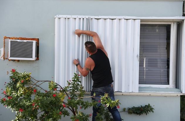 Anthony Perrone barricade sa maison en préparation de l'ouragan Isaias, à Lake Worth, dans le sud de la Floride, le 31 juillet 2020 [JOE RAEDLE / GETTY IMAGES NORTH AMERICA/AFP]