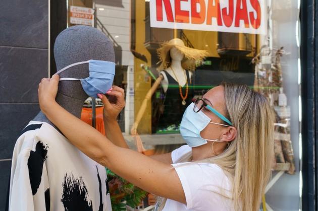 Une vendeuse place un masque sur un mannequin à Aranda de Duero, le 7 août 2020 en Espagne [CESAR MANSO / AFP]