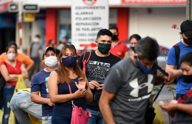 Des personnes attendent à un arrêt de bus à Asuncion (Paraguay) le 28 août 2020 [NORBERTO DUARTE / AFP]
