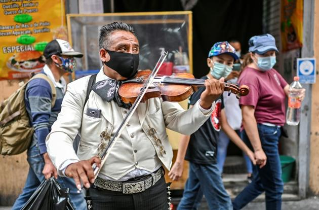 Un mariachi se produit dans une rue de Mexico, le 7 août 2020 [Pedro PARDO / AFP]
