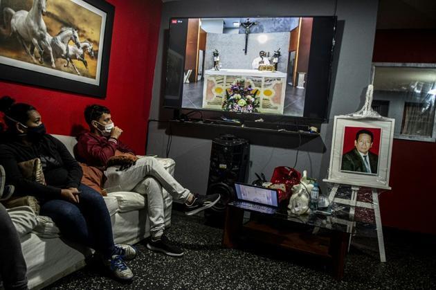 Les membres de la famille Diaz assistent à une messe en ligne à la mémoire de leur père Cecilio Diaz mort du coronavirus il y a un mois, le 11 août 2020 à Chorrillos, au sud de Lima, au Pérou [Ernesto BENAVIDES / AFP]