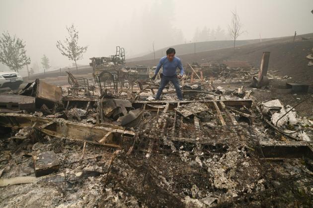 Marcelino Maceda fouille dans les décombres de son mobile home à Estacada (Oregon) le 12 septembre 2020 [Robyn Beck / AFP]