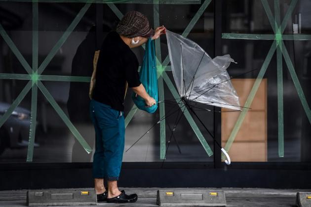 Un homme tient son parapluie brisé alors que le typhon Haishen approche de Kagoshima, au Japon, le 6 septembre 2020<br />  [CHARLY TRIBALLEAU / AFP]