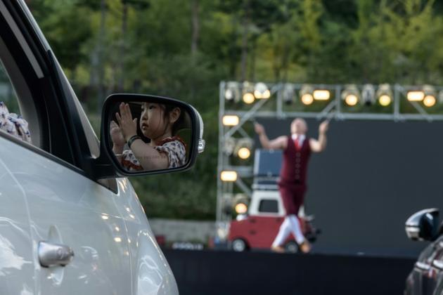 Un artiste se produit lors d'une représentation de cirque en drive-in devant des automobilistes à Séoul, le 19 septembre 2020 [- / AFP]