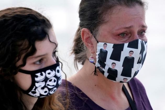 Deux femmes rendent hommage à Ruth Bader Ginsburg, dont l'une avec un masque à l'effigie de la juge défunte, à Washington, le 23 septembre 2020 [Andrew Harnik / POOL/AFP]