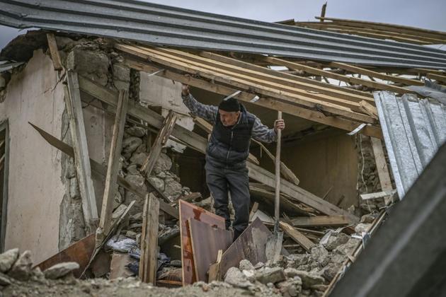 Un habitant dans les ruines de sa maison détruite par un bombardement, le 10 octobre 2020 à Stepanakert, au Nagorny-Karabakh [ARIS MESSINIS / AFP]