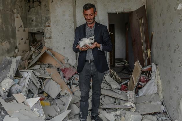 Un homme tient un chaton trouvé dans les ruines de son apartement après un bombardement, le 10 octobre 2020 à Tartar, en Azerbaïdjan [Bulent Kilic / AFP]