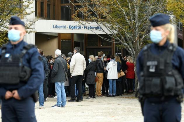 Recueillement devant l'école de Conflans-Sainte-Honorine, le 17 octobre 2020 au lendemain de l'assassinat par décapitation d'un de ses enseignants [Bertrand GUAY / AFP]