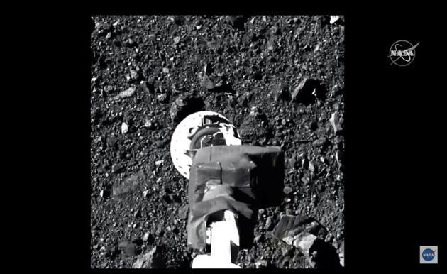 Cette image montre le bras de la sonde Osiris-Rex, pointée vers le sol de l'astéroïde, juste avant le contact, le 20 octobre 2020 [Handout / NASA TV/AFP]