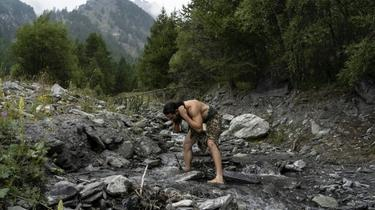 Un homme habillé comme un homme de Neanderthal se lave dans une rivière des Alpes italiennes [MARCO BERTORELLO / AFP/Archives]